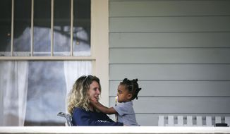 DeAnna Cooper sits on the porch with her daughter Ryan Brent,2, in Brady Heights Thursday, March 19, 2020. The family was practicing social distancing due to the coronavirus outbreak. (Mike Simons/Tulsa World/Tulsa World via AP)