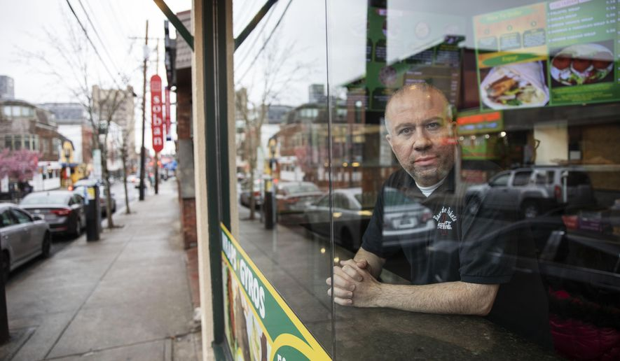 """Paul Boutros, owner of East Side Pockets, a small restaurant near Brown University, looks out onto an empty street since students were sent home two weeks ago, Wednesday, March 25, 2020, in Providence, R.I. """"He's not being realistic. How can you open if the cases are climbing day after day?"""" asked Boutros on Trump's call to restart the economy by mid-April. """"You go to Walmart, you don't know if the people around you, if they have the virus. People come to our restaurant. I don't know if they have the virus."""" (AP Photo/David Goldman)"""
