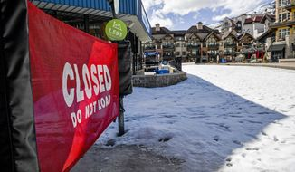 """In this Tuesday, March 24, 2020, photo a sign hangs on a closed ski lift in Vail, Colo., after Vail Ski Resort closed for the season amid the COVID-19 pandemic. Ski resorts across the West that were shut down amid coronavirus fears are grappling with an economic """"body blow"""" at a time when they normally would be welcoming hoards of spring break revelers. (AP Photo/Michael Ciaglo)"""