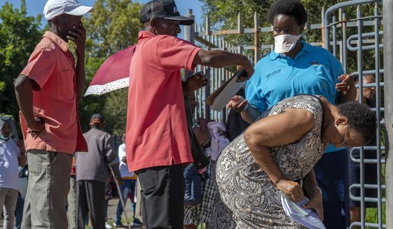 People seeking medical assistance queue outside a local clinic in the township of Soweto, near Johannesburg, South Africa, Thursday March 26, 2020, just hours before South Africa goes into a nationwide lockdown for 21 days, in an effort to control the spread to the coronavirus. The new coronavirus causes mild or moderate symptoms for most people, but for some, especially older adults and people with existing health problems, it can cause more severe illness or death. (AP Photo/Jerome Delay)