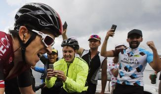FILE - In this file photo taken on July 25, 2019 spectators cheer Britain's Geraint Thomas climbing the Galibier pass during the eighteenth stage of the Tour de France cycling race between Embrun and Valloire. Swarms of fans clog the city streets, winding roads and soaring mountain passes of the Tour de France during cycling's three-week showpiece. But unlike almost every other major sporting event it has yet to be called off because of the coronavirus and the start date remains June 27. The new coronavirus causes mild or moderate symptoms for most people, but for some, especially older adults and people with existing health problems, it can cause more severe illness or death. (AP Photo/ Christophe Ena, File)