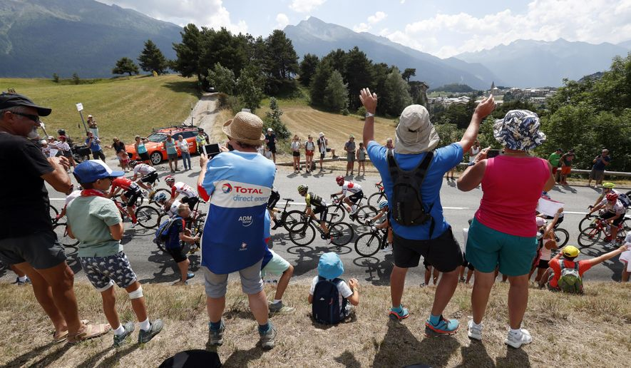 In this file photo taken on July 26, 2019, spectators along the road applaud the riders during the 19th stage of the Tour de France cycling race between Saint Jean De Maurienne and Tignes. (AP Photo/Thibault Camus, File)