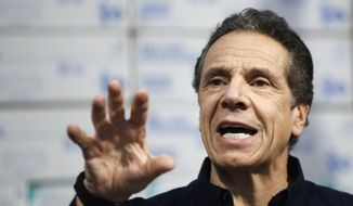 In this March 24, 2020, photo, New York Gov. Andrew Cuomo speaks during a news conference against a backdrop of medical supplies at the Jacob Javits Center that will house a temporary hospital in response to the COVID-19 outbreak in New York. (AP Photo/John Minchillo)