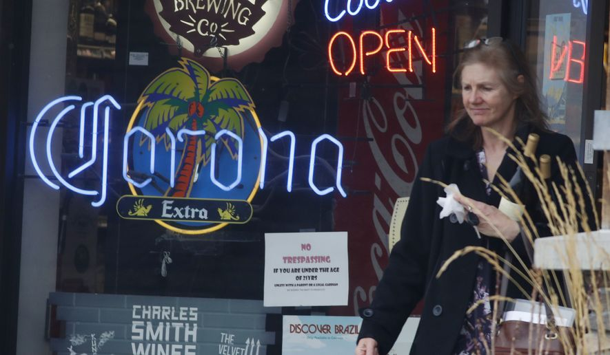 A customer walks past a sign advertising Corona beer while exiting a liquor store as a statewide stay-at-home order rollis into its second day of enforcement in an effort to reduce the spread of the new coronavirus Friday, March 27, 2020, in Bergen Park, Colo. The new coronavirus causes mild or moderate symptoms for most people, but for some, especially older adults and people with existing health problems, it can cause more severe illness or death. (AP Photo/David Zalubowski)