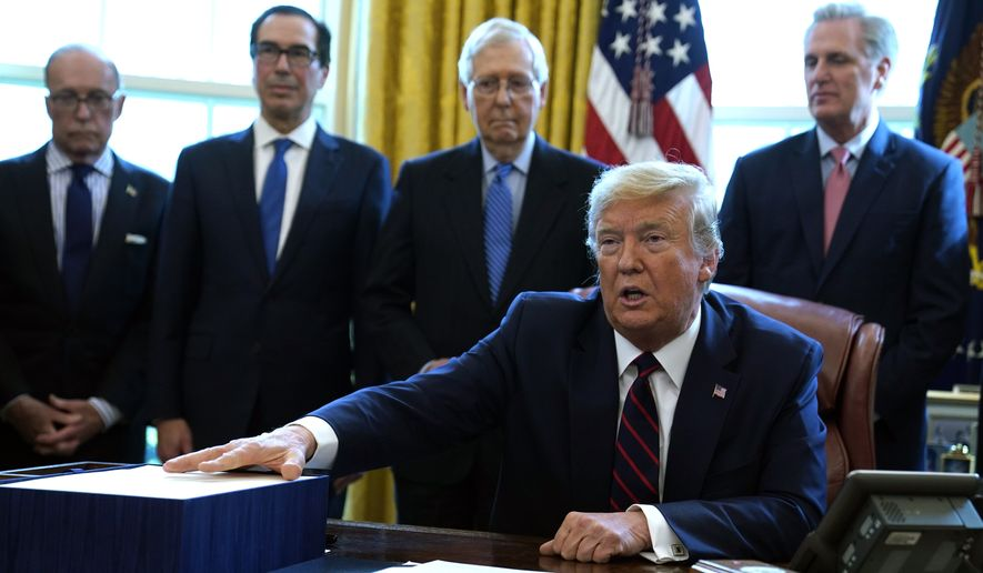 President Donald Trump speaks before he signs the coronavirus stimulus relief package in the Oval Office at the White House, Friday, March 27, 2020, in Washington. Listening are from left, Larry Kudlow, White House chief economic adviser, Treasury Secretary Steven Mnuchin, Senate Majority Leader Mitch McConnell, R-Ky., and House Minority Leader Kevin McCarty of Calif. (AP Photo/Evan Vucci)