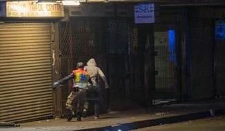 A police officer chases a man who violated the lockdown downtown Johannesburg, South Africa, Friday, March 27, 2020. Police and army started patrolling moments after South Africa went into a nationwide lockdown for 21 days in an effort to mitigate the spread to the coronavirus. The new coronavirus causes mild or moderate symptoms for most people, but for some, especially older adults and people with existing health problems, it can cause more severe illness or death.(AP Photo/Jerome Delay)