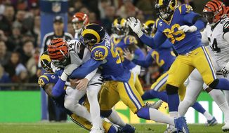 FILE - In this Oct. 27, 2019, file photo, Cincinnati Bengals quarterback Andy Dalton (14) is sacked by Los Angeles Rams defensive end Michael Brockers (90) and defensive end Dante Fowler (56) during the first half of an NFL football game at Wembley Stadium in London. A person familiar with the deal says the Atlanta Falcons have agreed to sign outside linebacker Dante Fowler. The person spoke to The Associated Press on condition of anonymity because free-agent signings can't be announced until after the league year begins Wednesday afternoon, March 18, 2020. (AP Photo/Tim Ireland, File)