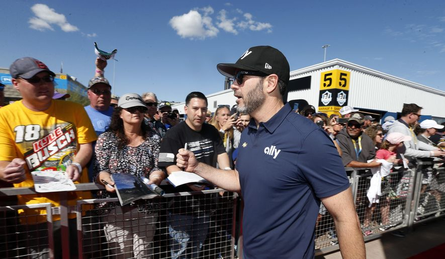 Driver Jimmie Johnson acknowledges fans as he walks to the drivers' meeting prior to a NASCAR Cup Series auto race at Phoenix Raceway, Sunday, March 8, 2020, in Avondale, Ariz. (AP Photo/Ralph Freso)  **FILE**