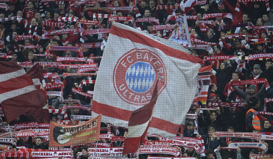 FILE - In this Wednesday, March 11, 2015 file photo, Bayern fans wave flags and scarfs before their Champions League soccer match against Shakhtar Donetsk in Munich, southern Germany. Even though the protests have stopped amid the coronavirus outbreak, many Bayern Munich fans are still pushing for their club to take its Qatari sponsor to task for human rights abuses in the country. Bayern is sponsored by state-owned carrier Qatar Airways and has been holding mid-season training camps in the Persian Gulf country since 2011.(AP Photo/Kerstin Joensson, file)