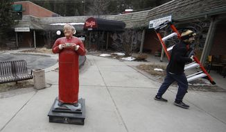 A worker passes by a sculpture outside a coffee shop open for pickup and take-away orders during a statewide stay-at-home order in an effort to reduce the spread of the new coronavirus Friday, March 27, 2020, in Evergreen, Colo. The new coronavirus causes mild or moderate symptoms for most people, but for some, especially older adults and people with existing health problems, it can cause more severe illness or death. (AP Photo/David Zalubowski)