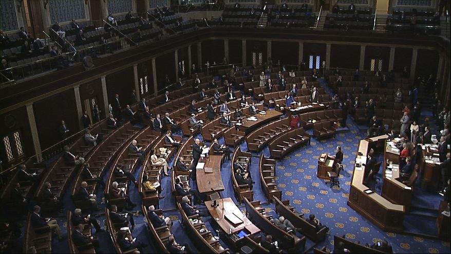 In this file image from video, members of the House practice social distancing as they sit on the floor and in the public gallery above during debate on the coronavirus stimulus package on the floor of the House of Representatives at the U.S. Capitol in Washington, Friday, March 27, 2020. (House Television via AP)