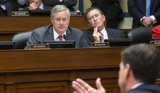 In this file photo from Thursday, July 7, 2016, Rep. Mark Meadows, R-N.C., left, and Rep. Thomas Massie, R-Ky., listen to FBI Director James Comey during a House Oversight Committee hearing at the Capitol in Washington. Meadows, currently President Donald Trump's acting-chief of staff, is still the sitting representative of North Carolina's 11th Congressional District in the House of Representatives as the body prepares to vote on massive relief funding to fight the Covid-19 pandemic, Friday, March 27, 2020. Party leaders had hoped to pass the measure by voice vote without lawmakers having to take the risk of traveling to Washington, but that plan might be complicated by Massie who could force a roll call vote. (AP Photo/J. Scott Applewhite, file)