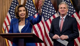 House Speaker Nancy Pelosi of Calif. accompanied by House Minority Leader Kevin McCarthy of Calif., right, speaks before signing the Coronavirus Aid, Relief, and Economic Security (CARES) Act after it passed in the House on Capitol Hill, Friday, March 27, 2020, in Washington. The $2.2 trillion package will head to head to President Donald Trump for his signature. (AP Photo/Andrew Harnik)