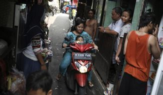 A motorist rides past as residents talk on an alley at a low-income neighborhood in Jakarta, Indonesia, March 23, 2020.As the virus spreads, the World Health Organization has pointed out that the future of the pandemic will be determined by what happens in some of the world's poorest and most densely populated countries. From Mumbai to Rio de Janeiro to Johannesburg the question is: What do you do if there is no space to socially distance yourself from others in some of world's most unequal regions? (AP Photo/Dita Alangkara)