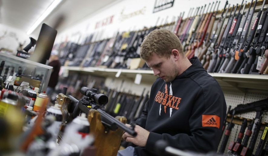 Todd Payne mounts a scope to a carbine rifle at Ross Coin and Gun on Monday, March 16, 2020, in Idaho Falls, Idaho. Just as grocery stores have been stripped bare by Americans panicked by coronavirus, guns and ammunition have started flying off the shelves. (John Roark/The Idaho Post-Register via AP)