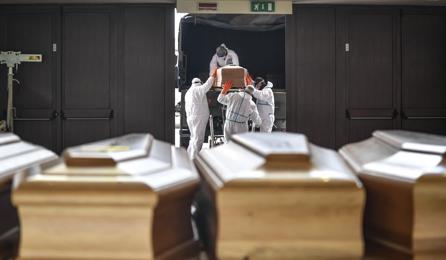 In this file photo, coffins arrive from the Bergamo area, where the coronavirus infections caused many victims, are being unloaded from a military truck that transported them in the cemetery of Cinisello Balsamo, near Milan in Northern Italy, Friday, March 27, 2020.   (Claudio Furlan/LaPresse via AP) **FILE**