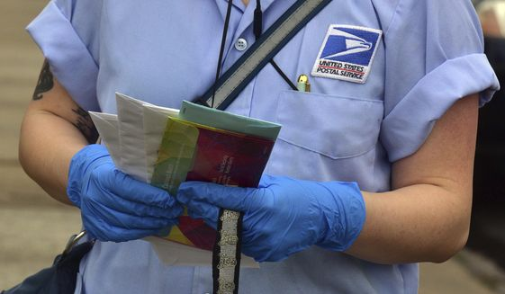 In this Friday March 20, 2020 file photo, a U.S Postal Service mail carrier wears gloves while delivering mail in South Wilkes-Barre, Pa. Health experts say the risks are very low that coronavirus will remain on envelopes or packages and infect anyone that comes in contact with it. But those on the frontlines of all those deliveries are taking steps to try to protect themselves. (Aimee Dilger/The Times Leader via AP)