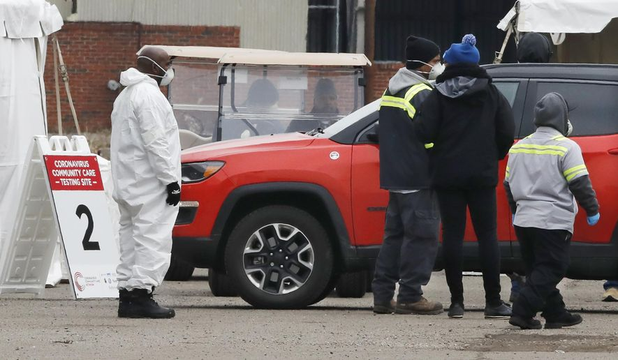 Health care officials watch as a vehicle approaches a testing site at the Michigan State Fairgrounds, Friday, March 27, 2020, in Detroit. The city set up several stations at the fairgrounds to allow for drive-up testing for the coronavirus. (AP Photo/Carlos Osorio) **FILE**
