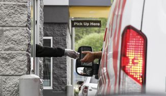 A cashier at the window of McDonald's in Meridian, Miss., takes a debit card from a customer with her gloved hand, Thursday, March 19, 2020. Most fast food restaurants are doing drive through, delivery and online order pick-ups only due to the coronavirus. (Paula Merritt/The Meridian Star via AP)