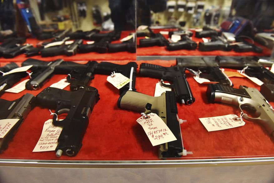 In this file photo, handguns sit in a display case at a gun store in Wilkes-Barre, Pa., Wednesday, March 18, 2020. (Sean McKeag/The Citizens' Voice via AP) **FILE**