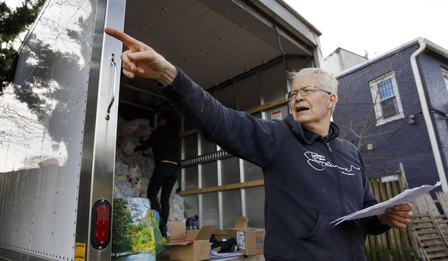 """Mark Andersen, 60, co-director of the nonprofit organization, """"We Are Family DC,"""" organizes groceries and food to be brought to seniors, Saturday, March 21, 2020, in Washington. Seniors are being encouraged to stay in their homes due to the risk of the COVID-19 coronavirus. (AP Photo/Jacquelyn Martin)"""