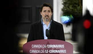 Prime Minister Justin Trudeau speaks during his daily press conference on COVID-19, in front of his residence at Rideau Cottage, on the grounds of Rideau Hall in Ottawa, on Saturday, March 28, 2020.  (Justin Tang/The Canadian Press via AP)