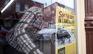 """In this Thursday, March 19, 2020 photo, a sign promoting the Grant County Historical Society Museum's """"Sonny Days in Lancaster"""" event is updated with a 'postponed' status by Cindy Busch at the museum in Lancaster, Wis. (John Hart/Wisconsin State Journal via AP)"""