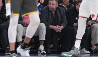 FILE - In this March 6, 2020, file photo, New York Knicks owner James Dolan, center, watches the first half of an NBA basketball game between the Knicks and the Oklahoma City Thunder at Madison Square Garden in New York. Dolan, the executive chairman of Madison Square Garden Company and owner of the Knicks, has tested positive for the coronavirus. The Knicks announced Dolan's diagnosis Saturday night, March 28. It is not clear when he was tested or when he received the diagnosis. (AP Photo/Mary Altaffer, File)