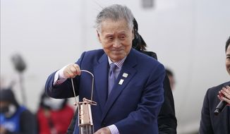 In this March 20, 2020, file photo, Tokyo 2020 Olympics chief Yoshiro Mori carries the Olympic flame during the Flame Arrival Ceremony at Japan Air Self-Defense Force Matsushima Base in Higashimatsushima in Miyagi Prefecture, north of Tokyo. Tokyo Olympic organizers seem to be leaning away from starting the rescheduled games in the spring of 2021. More and more the signs point toward the summer of 2021. Organizing committee President Mori suggested there would be no major change from 2020. (AP Photo/Eugene Hoshiko, File)  **FILE**