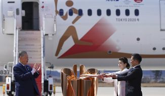 FILE - In this March 20, 2020, file photo, Olympic gold medalists Tadahiro Nomura, right, and Saori Yoshida light the torch as Tokyo 2020 Olympics chief Yoshiro Mori, left, watches during Olympic Flame Arrival Ceremony at Japan Air Self-Defense Force Matsushima Base in Higashimatsushima in Miyagi Prefecture, north of Tokyo. Tokyo Olympic organizers seem to be leaning away from starting the rescheduled games in the spring of 2021. More and more the signs point toward the summer of 2021. Organizing committee President Mori suggested there would be no major change from 2020.  (AP Photo/Eugene Hoshiko, File)