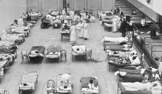 "In this 1918 file photo made available by the Library of Congress, volunteer nurses from the American Red Cross tend to influenza patients in the Oakland Municipal Auditorium, used as a temporary hospital. Woodrow Wilson did not address the nation on the subject of the pandemic of 1918-19 a single time, he did not call for Congress to act and he did not summon the nation to come together. (Edward A. ""Doc"" Rogers/Library of Congress via AP, File)"
