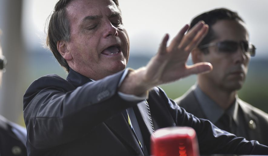 Brazil's President Jair Bolsonaro greets supporters and journalists as he arrives to give a news conference on the new coronavirus at Planalto presidential palace in Brasilia, Brazil, Friday, March 27, 2020. Even as coronavirus cases mount in Latin America's largest nation, Bolsonaro is calling the pandemic a momentary, minor problem and saying strong measures to contain it are unnecessary. (AP Photo/Andre Borges)