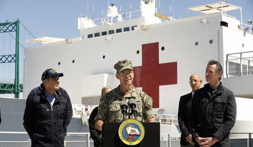 Los Angeles Mayor Eric Garcetti, left, and California Governor Gavin Newsom, right, listen as Adm. John Gumbleton, of the U.S. Navy, speaks in front of the hospital ship USNS Mercy that arrived into the Port of Los Angeles on Friday, March 27, 2020, to provide relief for Southland hospitals overwhelmed by the coronavirus pandemic. (Carolyn Cole/Los Angeles Times via AP, Pool) ** FILE **