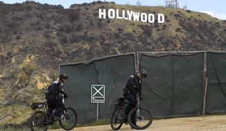 Los Angeles police officers patrol near the Hollywood Sign, Saturday, March 28, 2020, in Los Angeles. With cases of coronavirus surging and the death toll surpassing 100, lawmakers are pleading with cooped-up Californians to spend a second weekend at home to slow the spread of the infections. It has been more than a week since Gov. Gavin Newsom barred 40 million residents from going outdoors except for essentials. Even so, reports of crowds have prompted local and state officials to warn that ignoring social distancing, park and beach closures could spread the virus, which already is surging.  (AP Photo/Mark J. Terrill)