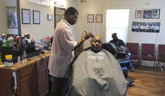 In this March 26, 2020, Patrick Goodman cuts Keith Donaldson's hair at Creative Image barber shop in Columbia, SC. South Carolina's governor has not given a stay at home order closing non-essential businesses, but Columbia did pass an order, which will close Goodman's shop. (AP Photo /Jeffrey Collins).