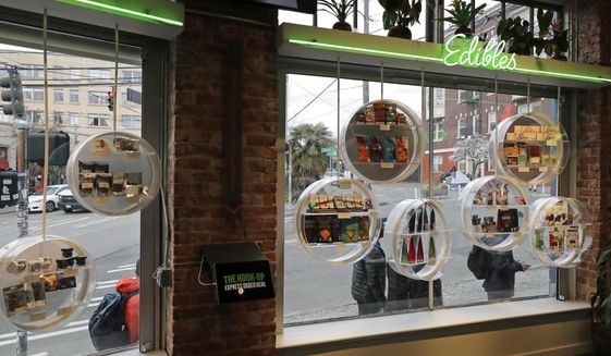 In this photo taken March 24, 2020, customers line up on the sidewalk outside The Reef Capitol Hill, a marijuana store in Seattle and observe social distancing chalk marks on the sidewalk as they wait to get into the store, which was limiting the number of people inside at one time to help slow the spread of the new coronavirus. (AP Photo/Ted S. Warren)