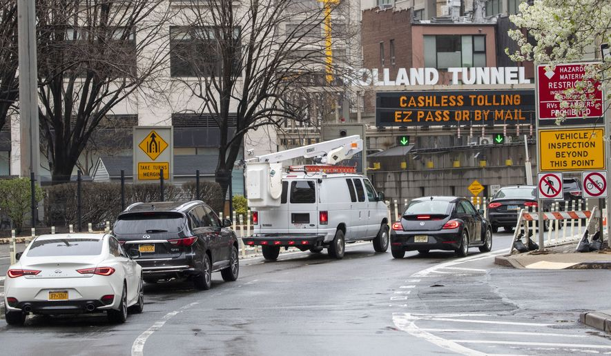 Cars make their way to New Jersey as they enter the Holland Tunnel from Canal St., Sunday, March 29, 2020, in New York. On Saturday, after saying he was weighing the idea of a mandatory quarantine for New York, New Jersey and Connecticut, President Donald Trump tweeted that instead he'd issue advisory urging people in those states to avoid any nonessential travel for two weeks. The new coronavirus causes mild or moderate symptoms for most people, but for some, especially older adults and people with existing health problems, it can cause more severe illness or death. (AP Photo/Mary Altaffer)