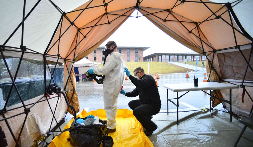 Sgt. First Class Mason Lord, with the Vermont Army National Guard, helps remove a personal protective equipment suit in a decontamination zone at the COVID-19 testing facility in a parking lot of Landmark College, in Putney, Vt., that was set up to test people with mild to moderate symptoms of the virus on Sunday, March 29, 2020. (Kristopher Radder/Brattleboro Reformer via AP)