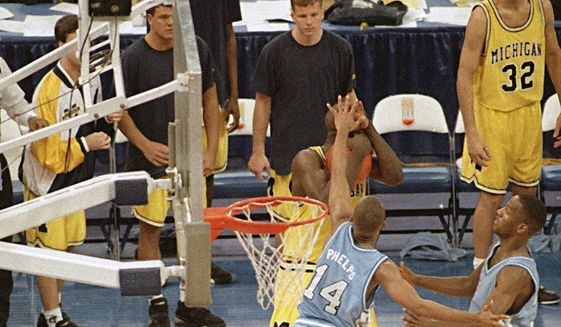 In this April 5, 1993 file photo, Michigan's Chris Webber, guarded by North Carolina's Derrick Phelps (14), calls a timeout in the closing moments of the NCAA Final Four championship game at the Superdome in New Orleans. Webber was called for a technical foul because they had no time outs left and North Carolina went on to win, 77-71. (AP Photo/Bill Haber, File)   **FILE**