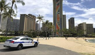 A police officer arrives to tell people to leave Waikiki Beach in Honolulu on Saturday, March 28, 2020. Like many cities across the world, Honolulu came to an eerie standstill this weekend as the coronavirus pandemic spread throughout the islands. (AP Photo/Caleb Jones) **FILE**