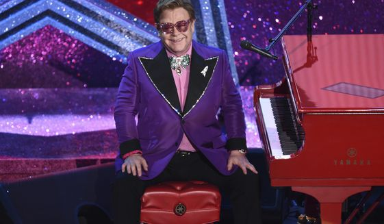 """FILE - In this Sunday, Feb. 9, 2020, file photo, Elton John is seen after performing """"(I'm Gonna) Love Me Again,"""" nominated for the award for best original song from """"Rocketman"""" at the Oscars at the Dolby Theatre in Los Angeles. John hosted an hour-long, live benefit concert special put on to raise money during the coronavirus crisis, Sunday, March 29, 2020, on Fox and iHeartMedia radio stations. (AP Photo/Chris Pizzello, File)"""