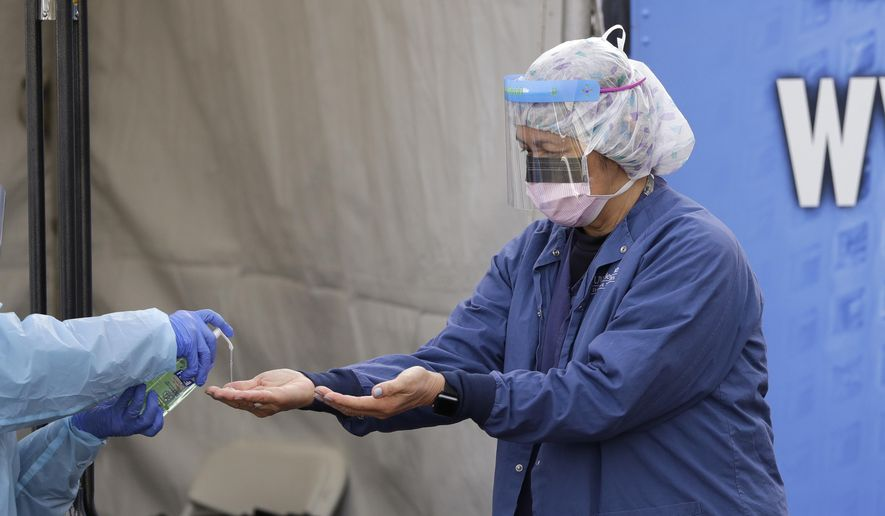 In this March 17, 2020, photo, Theresa Malijan, a registered nurse, has hand sanitizer applied on her hands after removing her gloves after she took a nasopharyngeal swab from a patient at a drive-thru COVID-19 testing station for University of Washington Medicine patients in Seattle. The Associated Press has found that the critical shortage of testing swabs, protective masks, surgical gowns and hand sanitizer can be tied to a sudden drop in imports of medical supplies. (AP Photo/Elaine Thompson)