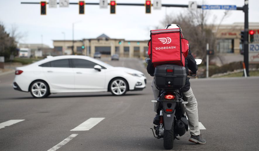 A food delivery rider waits for the traffic light to change to head northbound on Chester Street at County Line Road as a statewide stay-at-home order remains in effect in an effort to reduce the spread of the new coronavirus Monday, March 30, 2020, in Lone Tree, Colo. The new coronavirus causes mild or moderate symptoms for most people, but for some, especially older adults and people with existing health problems, it can cause more severe illness or death. (AP Photo/David Zalubowski)