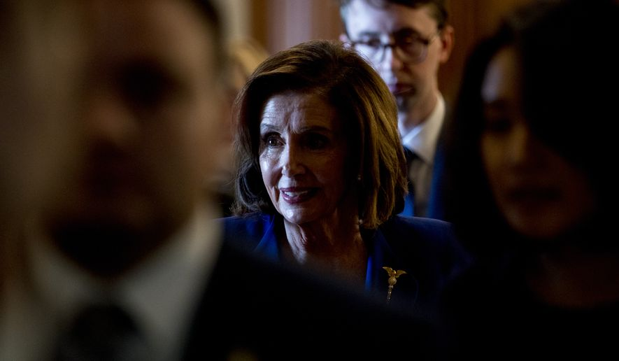 House Speaker Nancy Pelosi of Calif. leaves after signing the Coronavirus Aid, Relief, and Economic Security (CARES) Act after it passes in the House on Capitol Hill, Friday, March 27, 2020, in Washington. The $2.2 trillion package will head to head to Trump's desk for his signature. (AP Photo/Andrew Harnik)