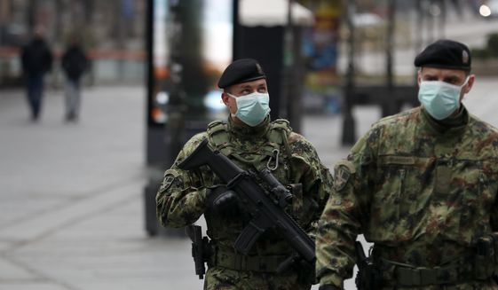 In this March 26, 2020, photo, Serbian army soldiers patrol in Belgrade's main pedestrian street, in Serbia. Since declaring a nationwide state of emergency, Serbian President Aleksandar Vucic has suspended parliament, giving him widespread powers such as closing borders and introducing a 12-hour curfew. (AP Photo/Darko Vojinovic)
