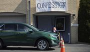 Father Bryce Evans hears confession at the drive-up confession site of St. Maron's Maronite Catholic Church in northeast Minneapolis Monday, March 39, 2020 as efforts continue to slow down the coronavirus in the state. The new coronavirus causes mild or moderate symptoms for most people, but for some, especially older adults and people with existing health problems, it can cause more severe illness or death. (AP Photo/Jim Mone)