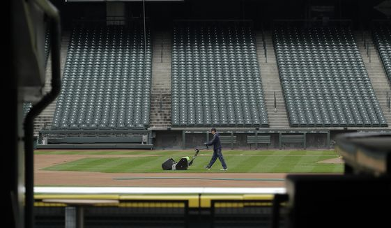 A grounds crew worker cuts the infield in front of empty seats at T-Mobile Park in Seattle, Thursday, March 26, 2020, around the time when the first pitch would have been thrown in the Mariners' Opening Day baseball game against the visiting Texas Rangers. Earlier in the month, Major League Baseball called off the start of the season due to the outbreak of the new coronavirus. (AP Photo/Ted S. Warren)  **FILE**