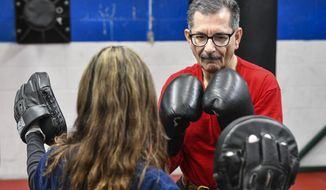 Joe Mehr works with instructor GraceMarie Tellone during a Rock Steady Boxing program class Wednesday, Feb. 5, 2020, at Downtown Gym & Fitness in St. Cloud, Minn. The program is designed to help people suffering from Parkinson's disease. (Dave Schwarz/The St. Cloud Times via AP)