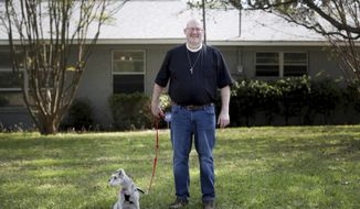 In this Thursday, March 26, 2020 photo, Rev. Dr. Robert Pace walks his dog outside of his home in Brenbook, Texas. Pace was the first known case of COVID-19 in Tarrant County. He has recovered and received his second negative test on March 19. (Amanda McCoy/Star-Telegram via AP)