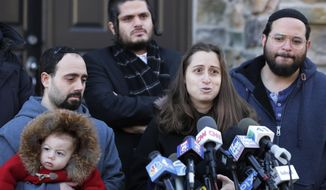 FILE - In this Jan. 2, 2020, file photo, surrounded primarily by family, Nicky Kohen, the daughter of Josef Neumann who was critically injured in an attack on a Hanukkah celebration, speaks to reporters in front of her home in New City, N.Y. An Orthodox Jewish organization said Neumann died Sunday, March 29, 2020, from his injuries three months after the attacks. (AP Photo/Seth Wenig, File)